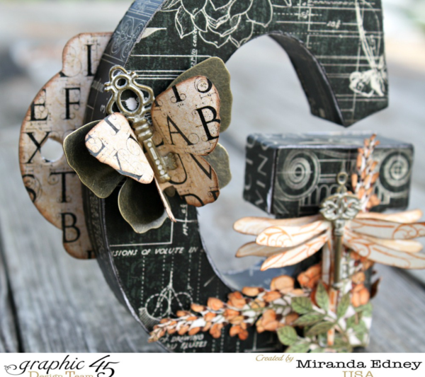 Dragonflies, flowers, and butterflies grace this gorgeous altered Artisan Style letter by Miranda Edney